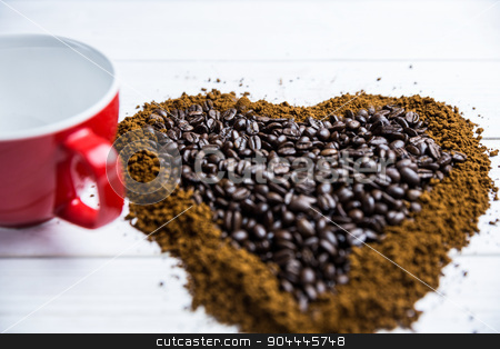 Coffee on a table in heart shape with cup stock photo, Coffee on a table in heart shape with cup shot in studio by Wavebreak Media