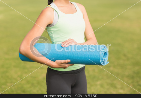Sporty woman holding exercise mat stock photo, Sporty woman holding exercise mat in parkland by Wavebreak Media