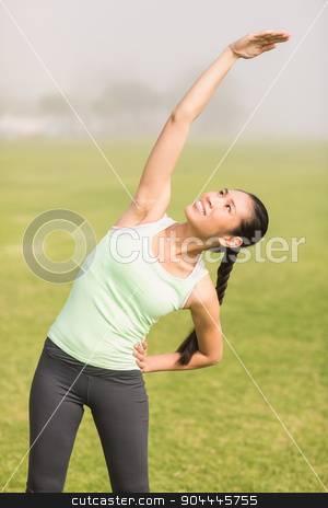 Sporty woman stretching arms stock photo, Sporty woman stretching arms in parkland by Wavebreak Media