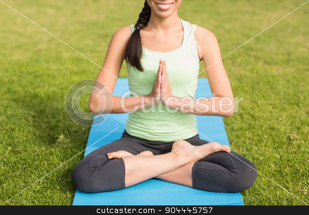 Smiling sporty woman doing the lotus pose stock photo, Smiling sporty woman doing the lotus pose in parkland by Wavebreak Media