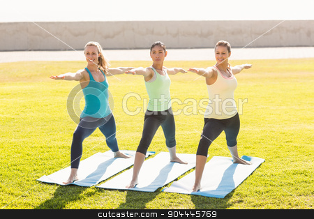 Smiling sporty women doing yoga together stock photo, Smiling sporty women doing yoga together in parkland by Wavebreak Media