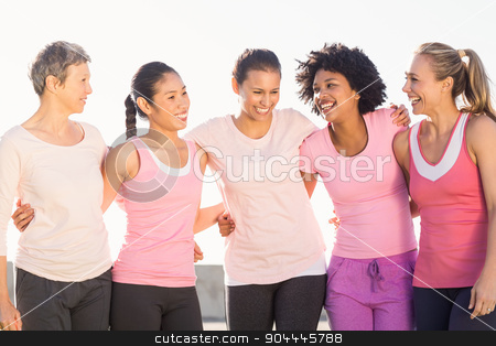 Laughing women wearing pink for breast cancer stock photo, Laughing women wearing pink for breast cancer in parkland by Wavebreak Media