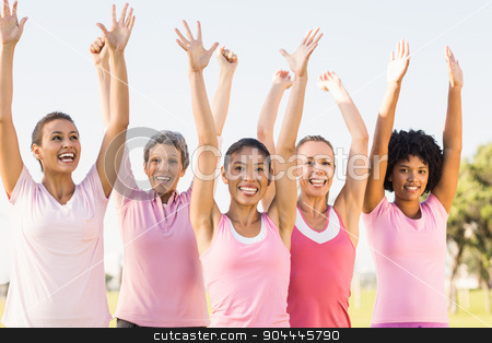 Smiling women wearing pink for breast cancer and cheering stock photo, Portrait of smiling women wearing pink for breast cancer and cheering in parkland by Wavebreak Media