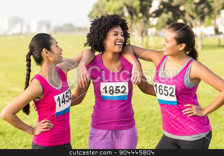 Three laughing runners supporting breast cancer marathon  stock photo, Three laughing runners supporting breast cancer marathon in parkland by Wavebreak Media