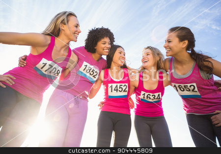 Five smiling runners supporting breast cancer marathon stock photo, Five smiling runners supporting breast cancer marathon in parkland by Wavebreak Media