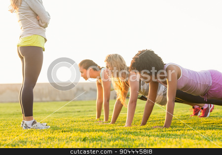Sporty women doing push ups during fitness class stock photo, Sporty women doing push ups during fitness class in parkland by Wavebreak Media
