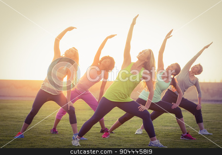 Sporty women warming up during fitness class stock photo, Sporty women warming up during fitness class in parkland by Wavebreak Media