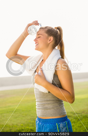 Sporty blonde cooling forehead with water bottle  stock photo, Sporty blonde cooling forehead with water bottle in parkland by Wavebreak Media