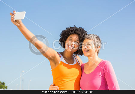 Two smiling sporty women taking selfies stock photo, Two smiling sporty women taking selfies at promenade by Wavebreak Media