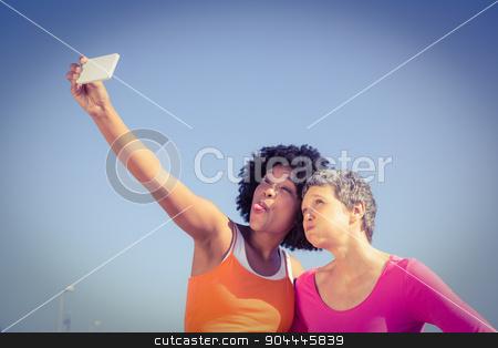 Two sporty women posing and taking selfies stock photo, Two sporty women posing and taking selfies at promenade by Wavebreak Media