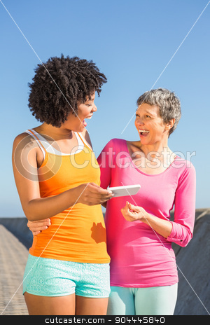 Two laughing sporty women looking at their selfies stock photo, Two laughing sporty women looking at their selfies at promenade by Wavebreak Media