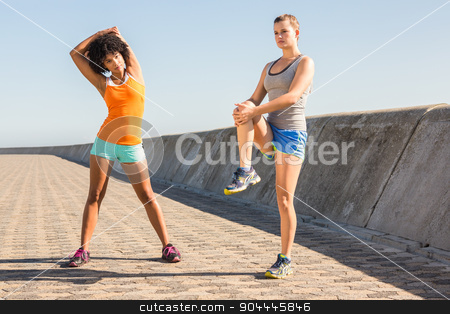 Two young woman stretching together stock photo, Two young woman stretching together at promenade by Wavebreak Media