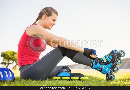 Smiling sporty blonde skater sitting in grass stock photo, Smiling sporty blonde skater sitting in grass at promenade by Wavebreak Media