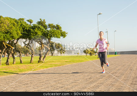 Focused sporty blonde jogging at promenade stock photo, Focused sporty blonde jogging at promenade on a sunny day by Wavebreak Media