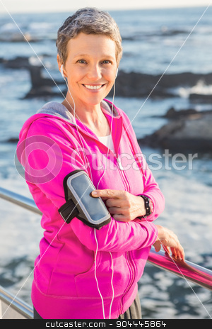 Smiling sporty woman enjoying music via headphones stock photo, Portrait of smiling sporty woman enjoying music via headphones at promenade by Wavebreak Media