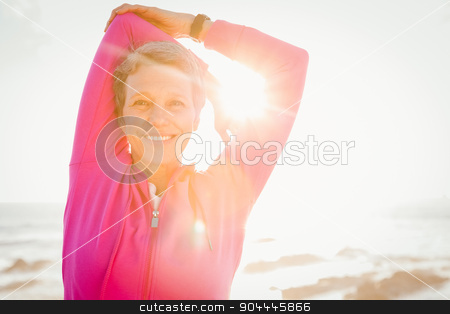 Smiling sporty woman stretching arms at promenade stock photo, Portrait of smiling sporty woman stretching arms at promenade on a sunny day by Wavebreak Media