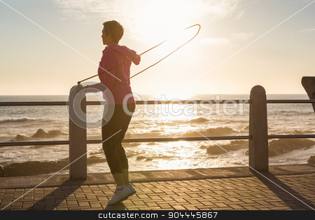 Sporty woman skipping at promenade stock photo, Sporty woman skipping at promenade on a sunny day by Wavebreak Media