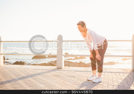 Breathing sporty woman resting at promenade stock photo, Breathing sporty woman resting at promenade on a sunny day by Wavebreak Media