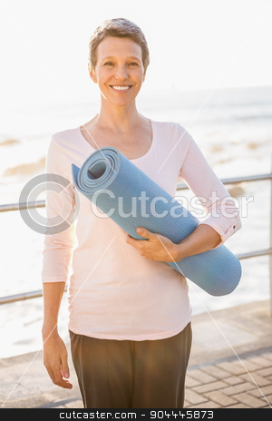 Smiling sporty woman with exercise mat stock photo, Portrait of smiling sporty woman with exercise mat at promenade by Wavebreak Media