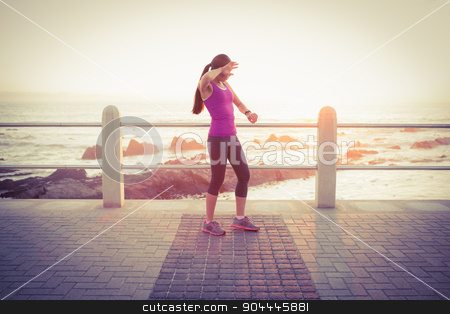 Tired fit woman checking smart watch at promenade stock photo, Tired fit woman checking smart watch at promenade on a sunny day by Wavebreak Media
