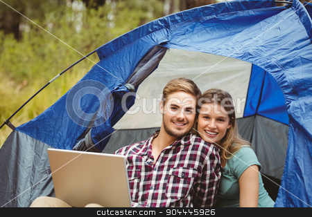 Young pretty hiker couple sitting in a tent looking at camera stock photo, Young pretty hiker couple sitting in a tent looking at camera in the nature by Wavebreak Media