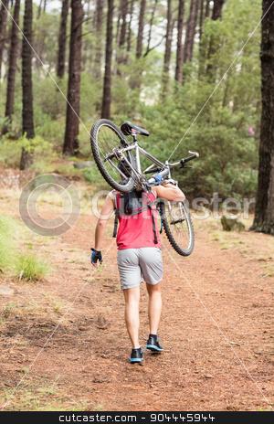 Happy handsome biker holding bike stock photo, Happy handsome biker holding bike in the nature by Wavebreak Media