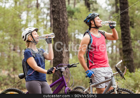 Happy handsome biker couple drinking water stock photo, Happy handsome biker couple drinking water in the nature by Wavebreak Media