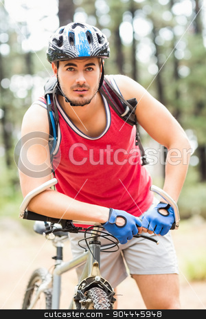 Handsome young biker looking at camera stock photo, Handsome young biker looking at camera in the nature by Wavebreak Media