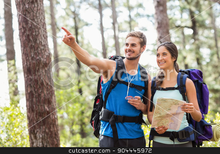 Happy hikers looking away holding map and compass stock photo, Happy hikers looking away holding map and compass in the nature by Wavebreak Media