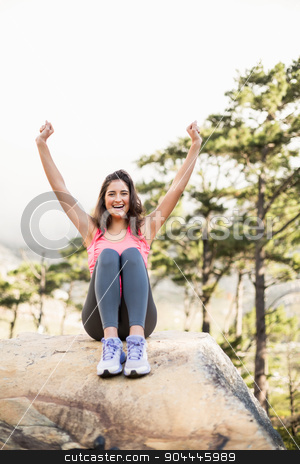 Young happy jogger sitting on rock cheering  stock photo, Young happy jogger sitting on rock cheering in the nature by Wavebreak Media