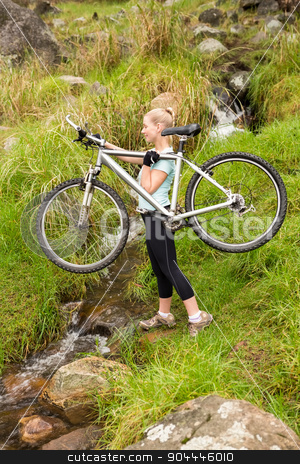Smiling fit woman lifting her bike stock photo, Smiling fit woman lifting her bike while crossing a river by Wavebreak Media