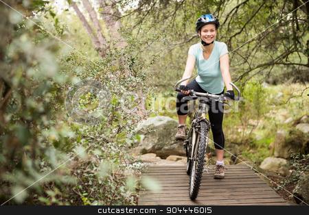 Smiling fit woman taking a break on her bike stock photo, Smiling fit woman taking a break on her bike on a wooden path by Wavebreak Media