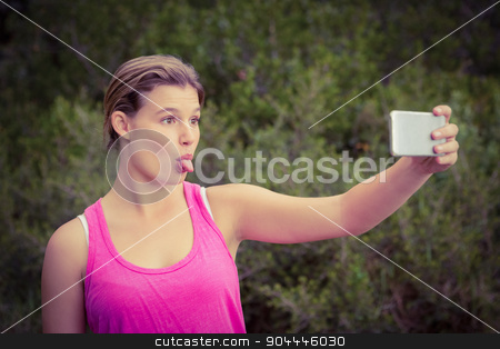 Pretty blonde athlete taking selfies with outstretched tongue stock photo, Pretty blonde athlete taking selfies with outstretched tongue in the nature by Wavebreak Media