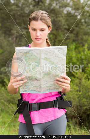 Blonde hiker with backpack reading map stock photo, Blonde hiker with backpack reading map in the nature by Wavebreak Media
