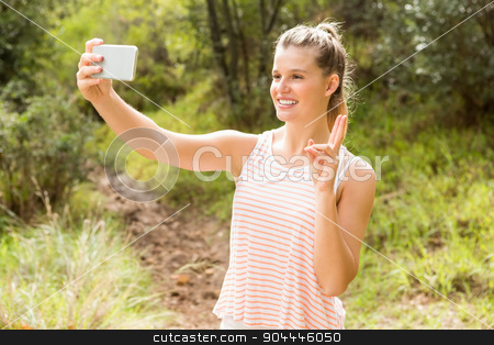 Pretty blonde showing peace sign and taking selfies stock photo, Pretty blonde showing peace sign and taking selfies in the nature by Wavebreak Media