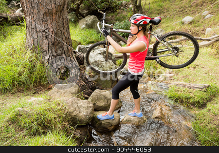 Blonde athlete carrying her mountain bike over stream stock photo, Blonde athlete carrying her mountain bike over stream in the nature by Wavebreak Media