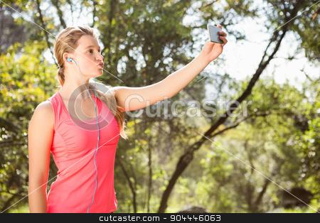 Blonde athlete sending kiss and taking selfies stock photo, Blonde athlete sending kiss and taking selfies in the nature by Wavebreak Media