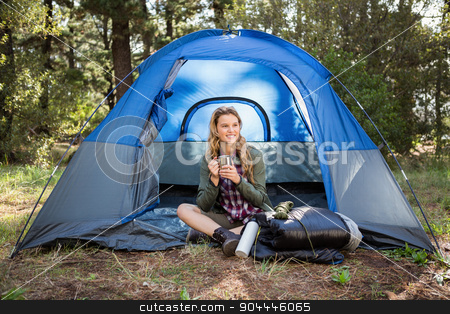 Pretty blonde camper smiling and sitting in tent stock photo, Pretty blonde camper smiling and sitting in tent in the nature by Wavebreak Media