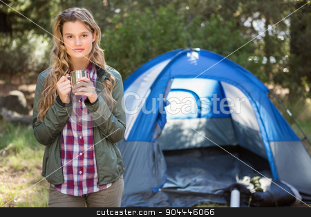 Pretty blonde camper standing in front of tent stock photo, Portrait of pretty blonde camper standing in front of tent in the nature by Wavebreak Media