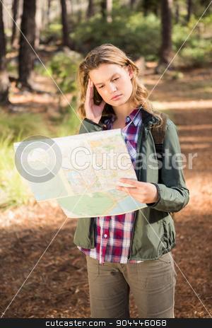 Pretty blonde hiker reading map  stock photo, Pretty blonde hiker reading map in the nature by Wavebreak Media