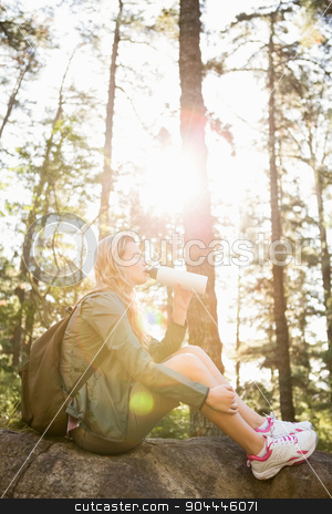 Pretty blonde hiker drinking and sitting on stone stock photo, Pretty blonde hiker drinking and sitting on stone in the nature by Wavebreak Media