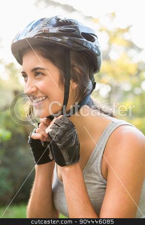 Smiling athletic brunette putting on helmet  stock photo, Smiling athletic brunette putting on helmet in the nature by Wavebreak Media