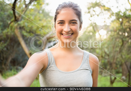 Smiling athletic brunette taking selfie stock photo, Portrait of smiling athletic brunette taking selfie in the nature by Wavebreak Media