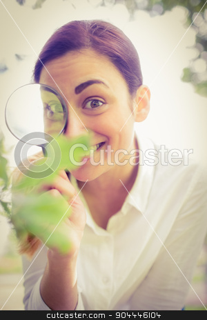 Beautiful brunette looking at plant through magnifying glass stock photo, Beautiful brunette looking at plant through magnifying glass on a sunny day by Wavebreak Media