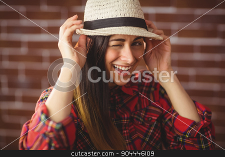 Beautiful hipster winking at camera stock photo, Beautiful hipster winking at camera on red brick background by Wavebreak Media