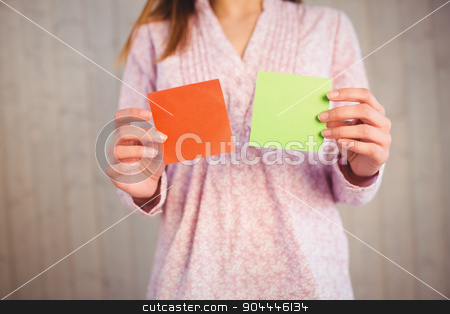 Woman holding green and orange cards stock photo, Woman holding green and orange cards on wooden planks background by Wavebreak Media