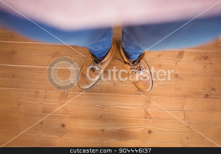 High angle view of woman wearing boots stock photo, High angle view of woman wearing boots on wooden planks background by Wavebreak Media