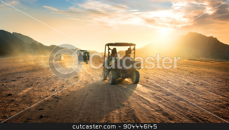 Buggies in desert stock photo, Buggies in sand desert at the sunset by Givaga