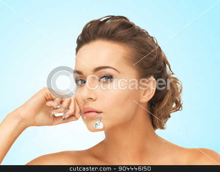 woman with diamond necklace stock photo, beautiful woman holding shiny diamond necklace in mouth by Syda Productions