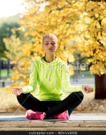 woman doing yoga outdoors stock photo, sport and lifestyle concept - woman doing yoga outdoors by Syda Productions
